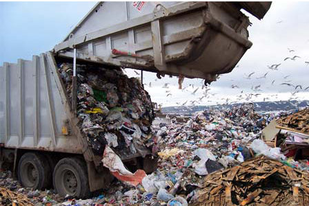 Garbage truck emptying trash into landfill