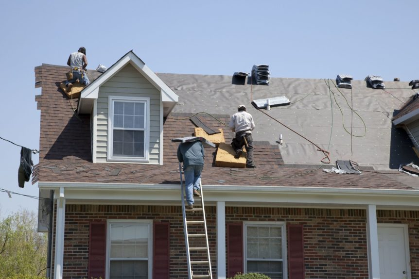 workers on the roof of a two story house