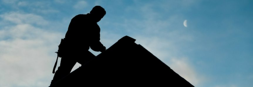 shadowed figure working on roof as a roofing contractor