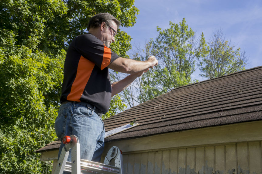 roofing contractor working to repair a roof of a client