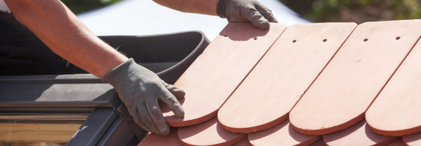 hands laying a roof shingle down on a roof