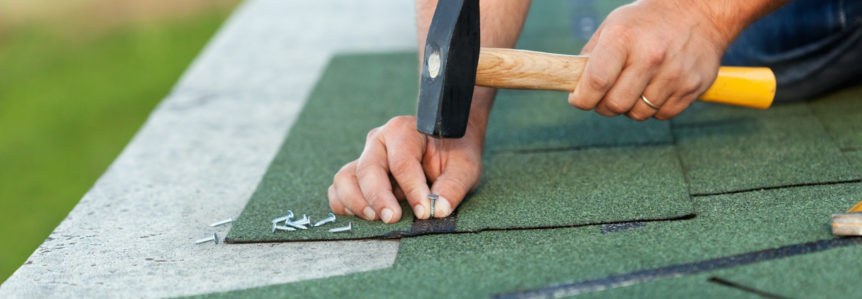 Hand hammering nail into green roof shingles