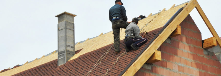 Two people repairing a roof after hurricane damage.